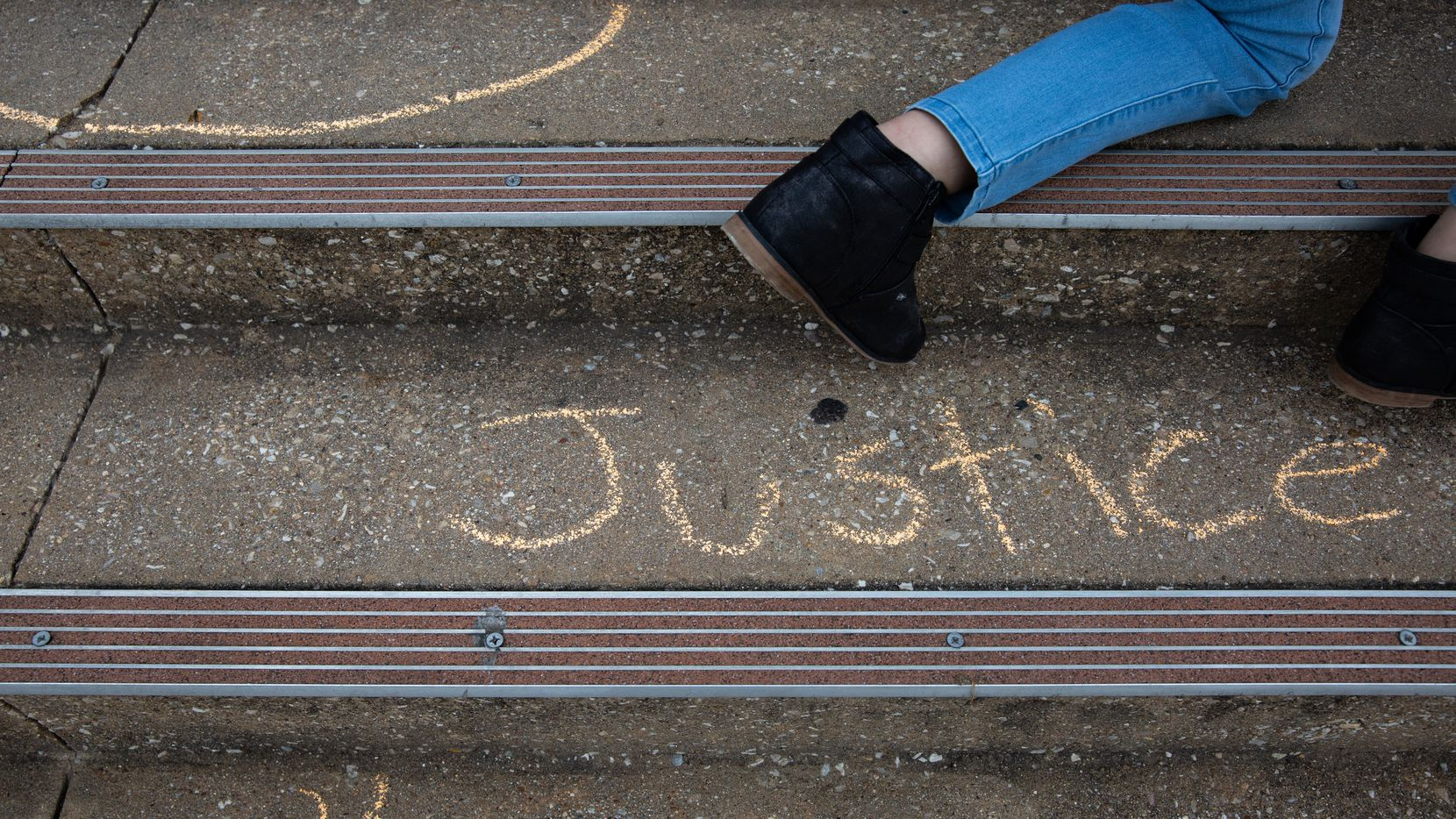 Demonstrators write with chalk on the stairs leading up to the Collin County Courthouse following a press conference on April 28, 2021 including updates on Marvin Scott III's death. Last week, the Fort Worth Star-Telegram broke news about another death in the jail.