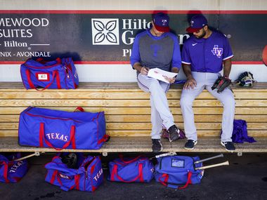 FILE - Rangers infielder Isiah Kiner-Falefa (right) goes over defensive positioning reports with major league field coordinator Corey Ragsdale before a spring training game against the Reds at Goodyear Ballpark on Monday, Feb. 24, 2020, in Goodyear, Ariz.