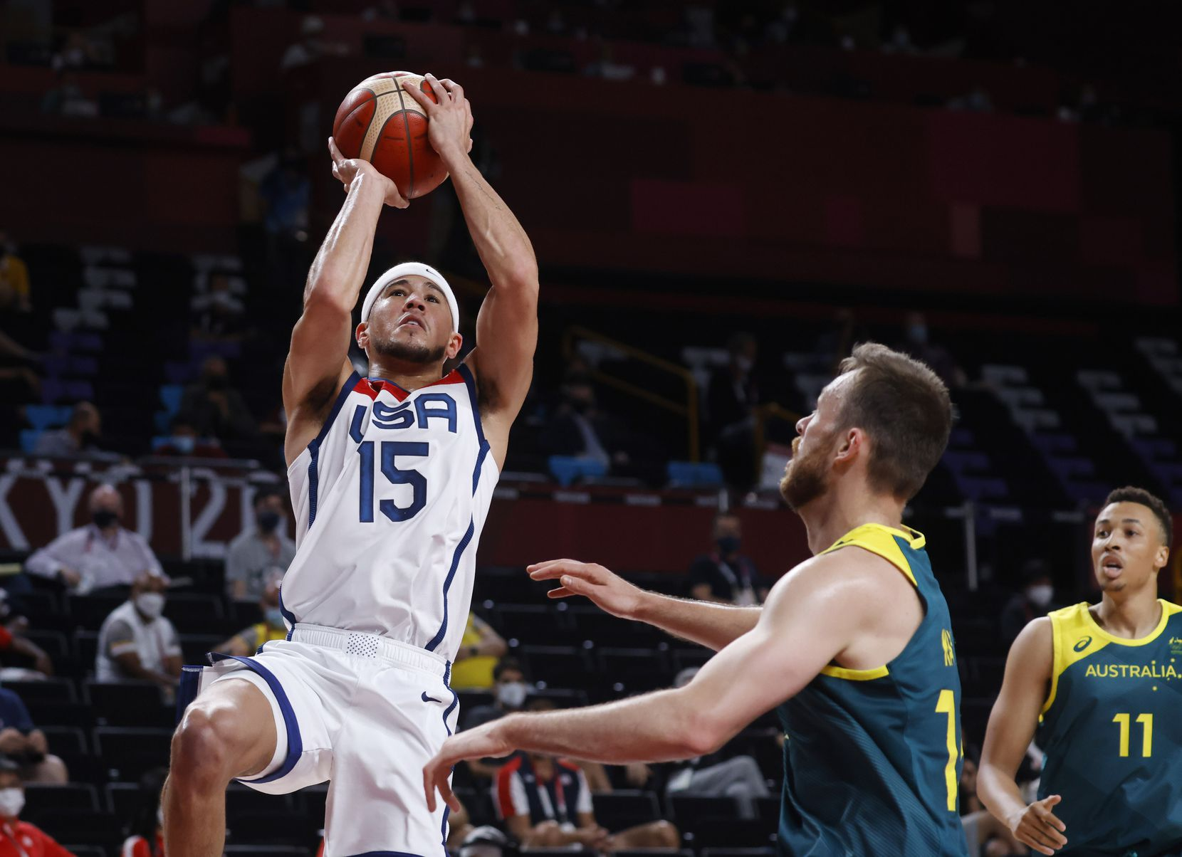 USA's Devin Booker attempts a shot in front of Australia's Nic Kay (15) during the first half of a men's basketball semifinal at the postponed 2020 Tokyo Olympics at Saitama Super Arena, on Thursday, August 5, 2021, in Saitama, Japan. USA defeated Australia 97-78 to advance to the gold medal game. (Vernon Bryant/The Dallas Morning News)