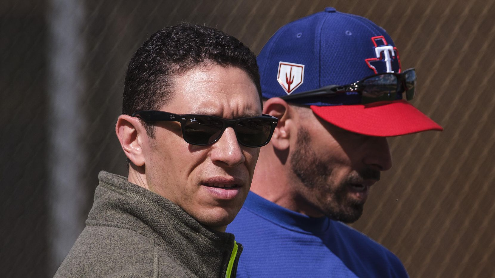 FILE - Rangers GM Jon Daniels (left) and manager Chris Woodward watch batting practice during the first full-squad spring training workout at the team's training facility on Monday, Feb. 18, 2019, in Surprise, Ariz.