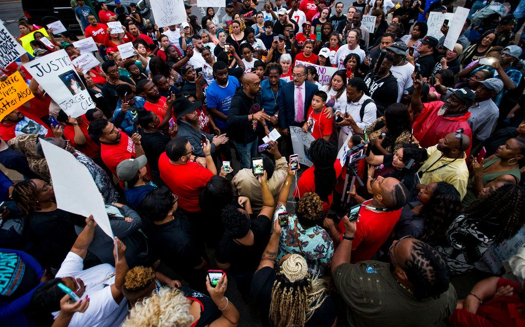 Frederick Douglass Haynes III talks to the crowd at Dallas police headquarters during a protest over the shooting of Botham Shem Jean. Jean's family in St. Lucia asked that protesters keep marching but keep the gatherings peaceful because that is what Jean would have wanted.