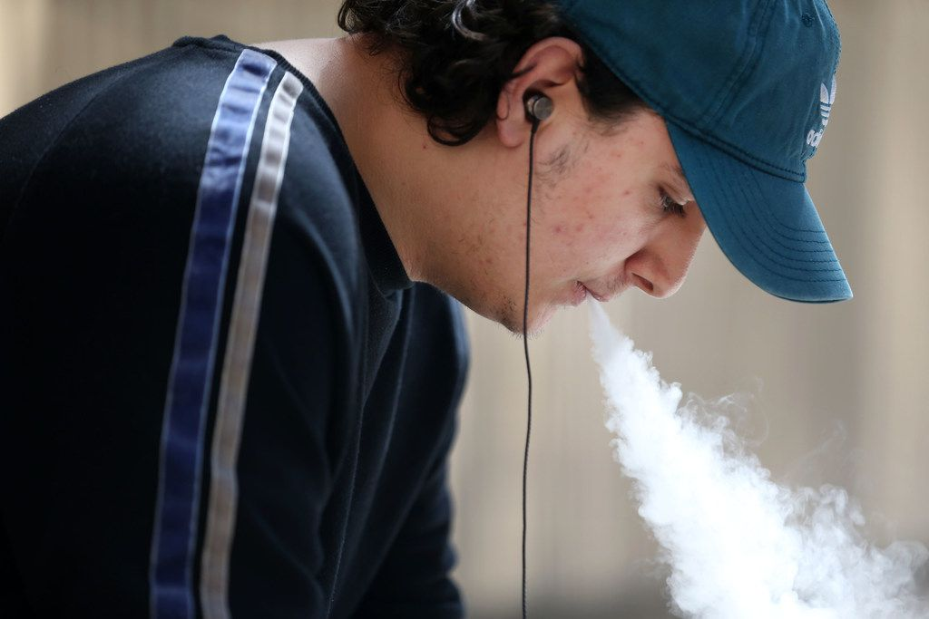 Aubrey Williams, 19, vapes outside El Centro College in downtown Dallas. Starting Sunday, the legal age for for buying cigarettes, other tobacco products and e-cigarettes changes from 18 to 21.