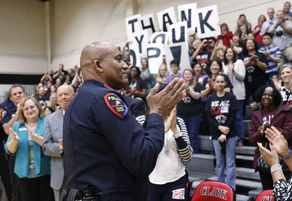 Plano police Officer Art Parker acknowledges people who honored him at Clark High School during a surprise pep rally on Monday. He was recently named Plano Police Officer of the Year. (David Woo/Staff Photographer)