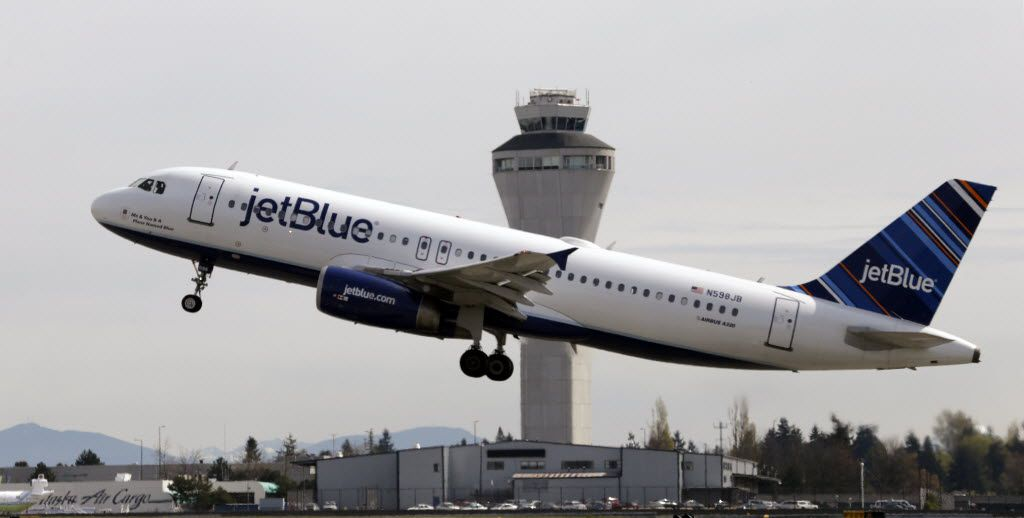 FILE - In this April 23, 2013, file photo, a JetBlue plane takes off in view of the air traffic control tower at Seattle-Tacoma International Airport, in Seattle. JetBlue, which has proudly proclaimed itself a holdout on fees for years, on Tuesday, June 30, 2015, said it will now charge up to $25 for checked luggage, although many passengers will pay less by planning ahead. (AP Photo/Elaine Thompson, File)