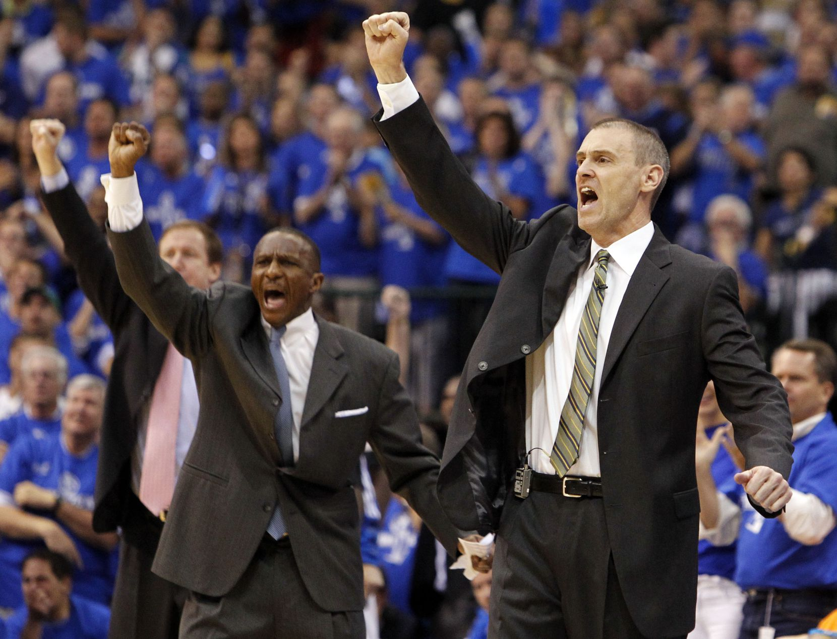 Dallas Mavericks head coach Rick Carlisle, and assistant coaches Dwane Casey (center) and Terry Stotts (far left) simultaneously use a hand signal to tell the Mavericks players on the floor to switch to zone defense, during the second quarter of play in game five of the NBA Finals against the Miami Heat at American Airlines Center Thursday, June 9, 2011 in Dallas.