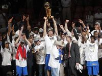 Dallas Mavericks team celebrate as the team is presented the Larry O'Brien NBA Championship trophy after winning game six of the NBA Finals between the Miami Heat and the Dallas Mavericks at the American Airlines Arena in Miami, Florida, June 12, 2011. Dallas Mavericks won 105-95. Dallas Mavericks power forward Dirk Nowitzki (41), Dallas Mavericks former owner Don Carter, Dallas Mavericks owner Mark Cuban, Dallas Mavericks shooting guard Jason Terry (31) and the rest of the team on the riser.