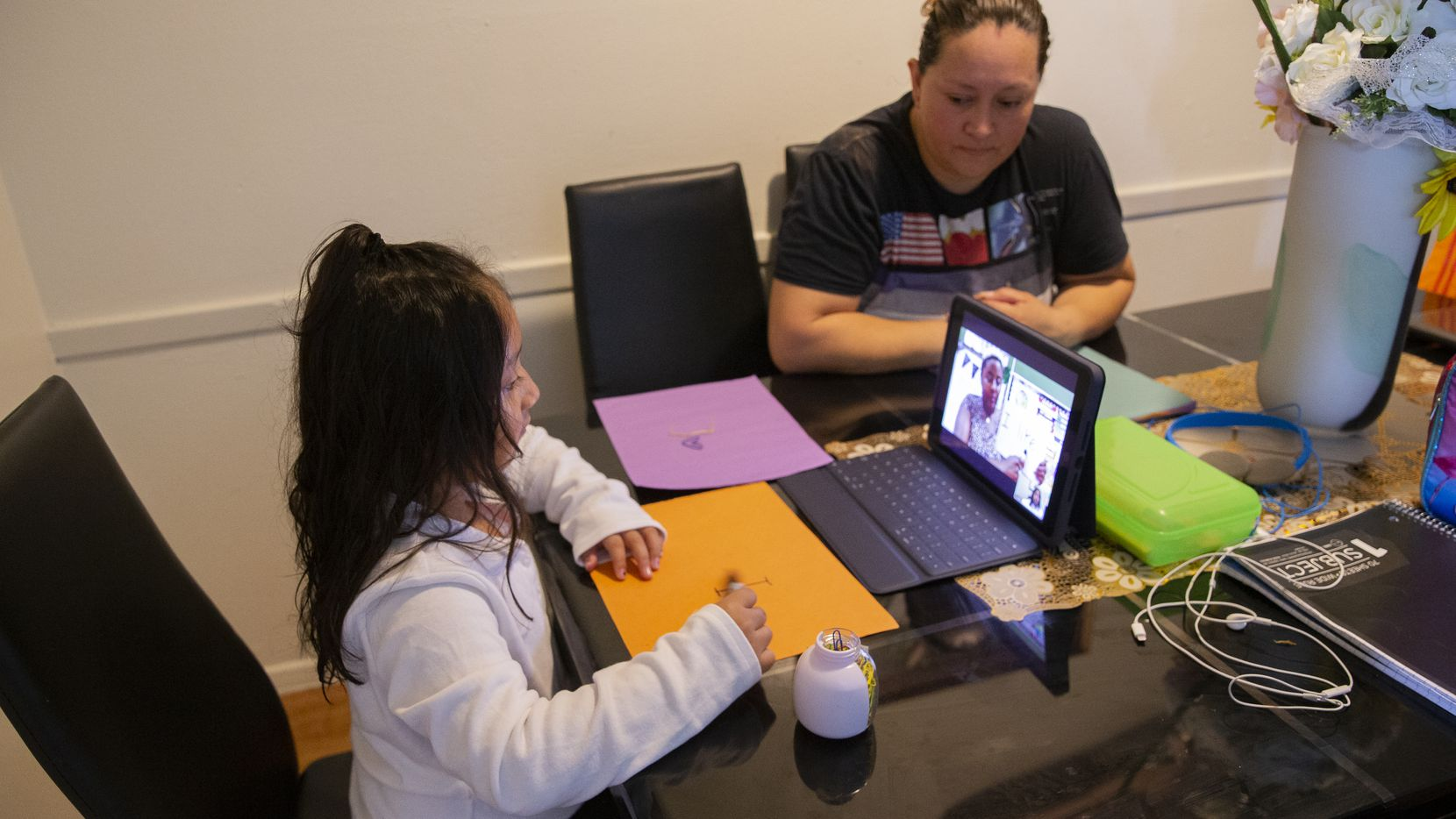 Adali Arriaza watches as her daughter Daysha Cojulum, 5, attends her virtual class at the kitchen table on Sept. 16, 2020 in northwest Dallas. Cojulum uses her mother's phone to connect to the internet due to the DISD hotspots not working properly or running out of the allotted data. (Juan Figueroa/ The Dallas Morning News)