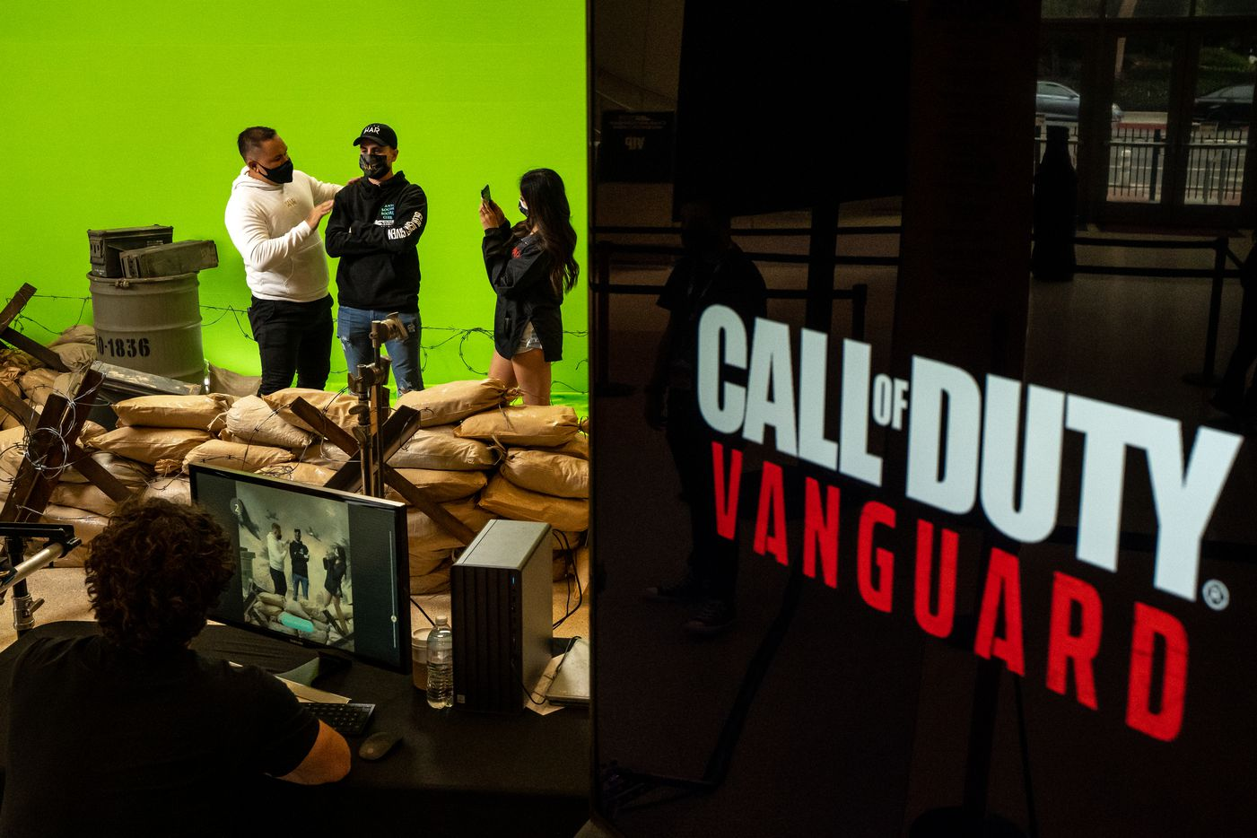 From left, Christian Bourdeax pretends to dust off Kevin Pichardo as Malee Mabandit takes a photo in a Call of Duty green screen booth to advertising the next game in the franchise, Call of Duty: Vanguard, on the final day of the Call of Duty league playoffs championship round at the Galen Center on Sunday, August 22, 2021 in Los Angeles, California. The Atlanta FaZe compete against Toronto Ultra in the championship round at 12pm PST. (Justin L. Stewart/Special Contributor)