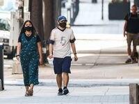 Una pareja portando mascarilla camina por las calles del centro de Dallas, el 21 de julio.
