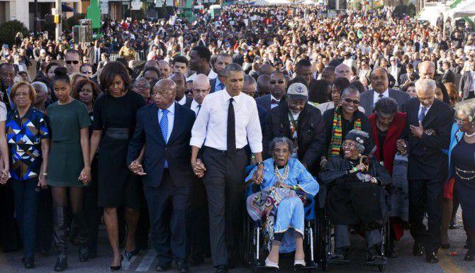 """El presidente Barack Obama toma la mano de Amelia Boynbton Robinson, quien fuera agredida en el """"Domingo Sangriento"""", durante la marcha para conmemorar los 50 años de los sucesos en Selma, Alabama. (AP/JACQUELYN MARTIN)"""