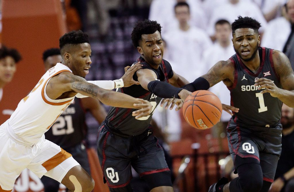 Texas guard Kerwin Roach II (12) battles Oklahoma guards Jamal Bieniemy (24) and Rashard Odomes (1) for a loose ball during the first half of an NCAA college basketball game, in Austin, Texas, Saturday, Jan. 19, 2019. (AP Photo/Eric Gay)