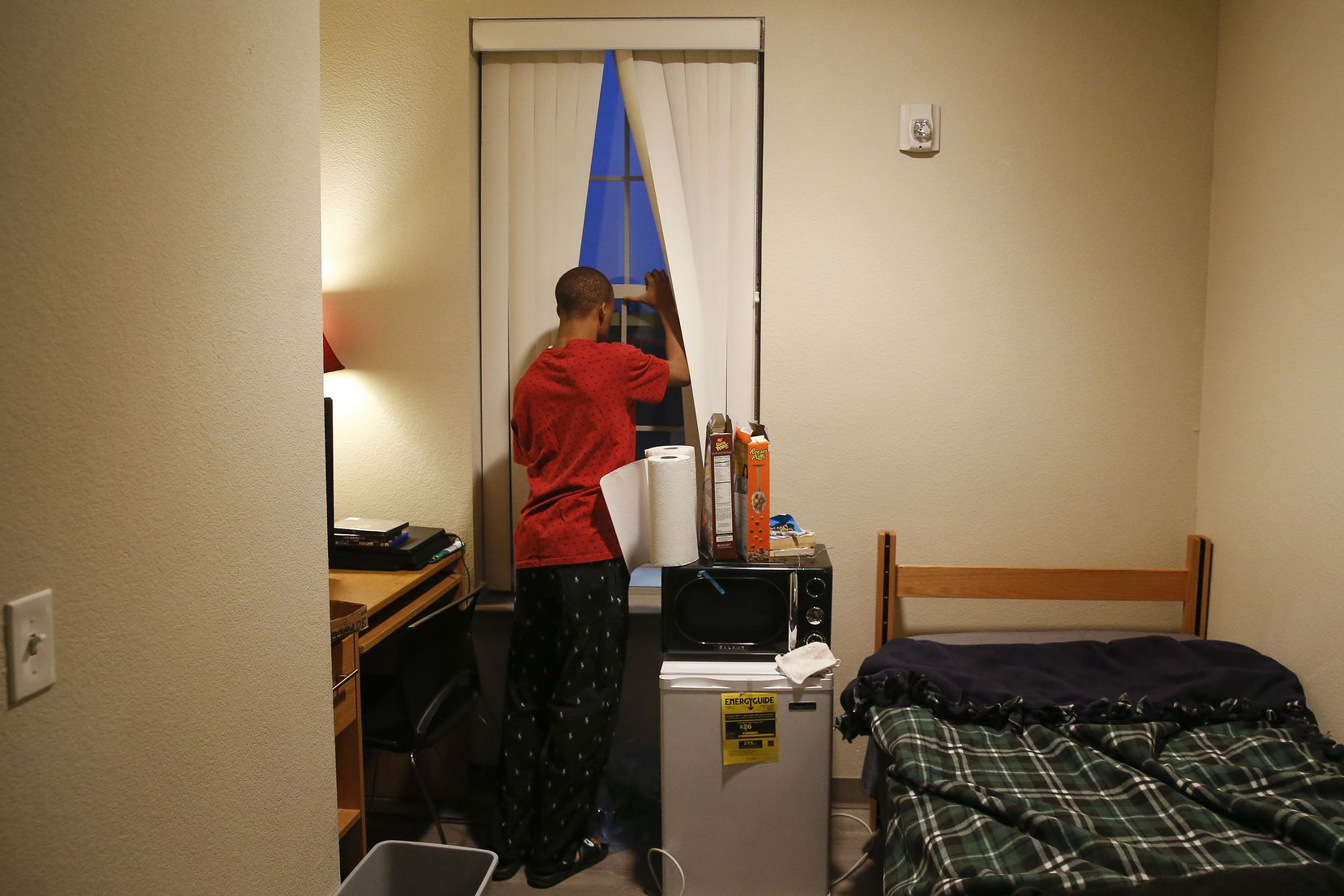 Jaylon Miller cracks his window for a breath of fresh air in his dorm room at the University of North Texas at Dallas. Miller rises daily, often before the sun, makes his bed, gets dressed, and completes his homework before heading off for class.