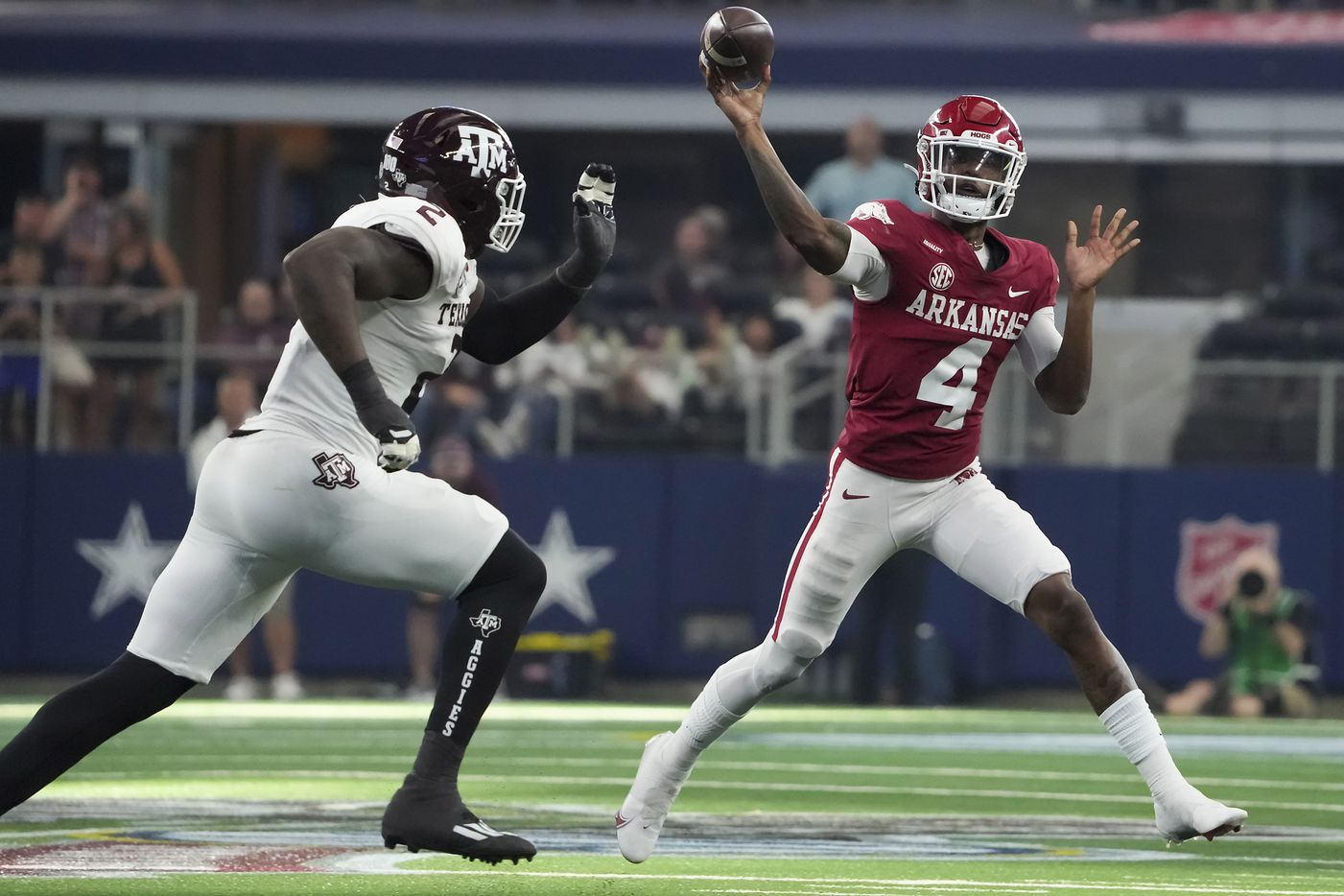 Arkansas quarterback Malik Hornsby (4) makes a pass as Texas A&M defensive lineman Micheal Clemons (2) applies pressure during the second half of an NCAA football game at AT&T Stadium on Saturday, Sept. 25, 2021, in Arlington. Arkansas won the game 20-10.