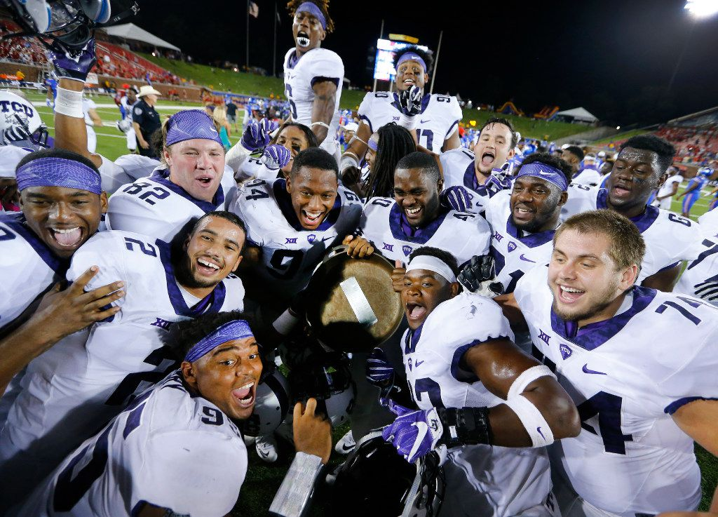 TCU Horned Frogs football players try to get into a group photo as they show off the Iron Skillet Award they maintain against the Southern Methodist Mustangs at Gerald J. Ford Stadium in University Park, Texas, Friday, September 23, 2016. TCU won the Battle of the Skillet, 33-3. (Tom Fox/The Dallas Morning News)