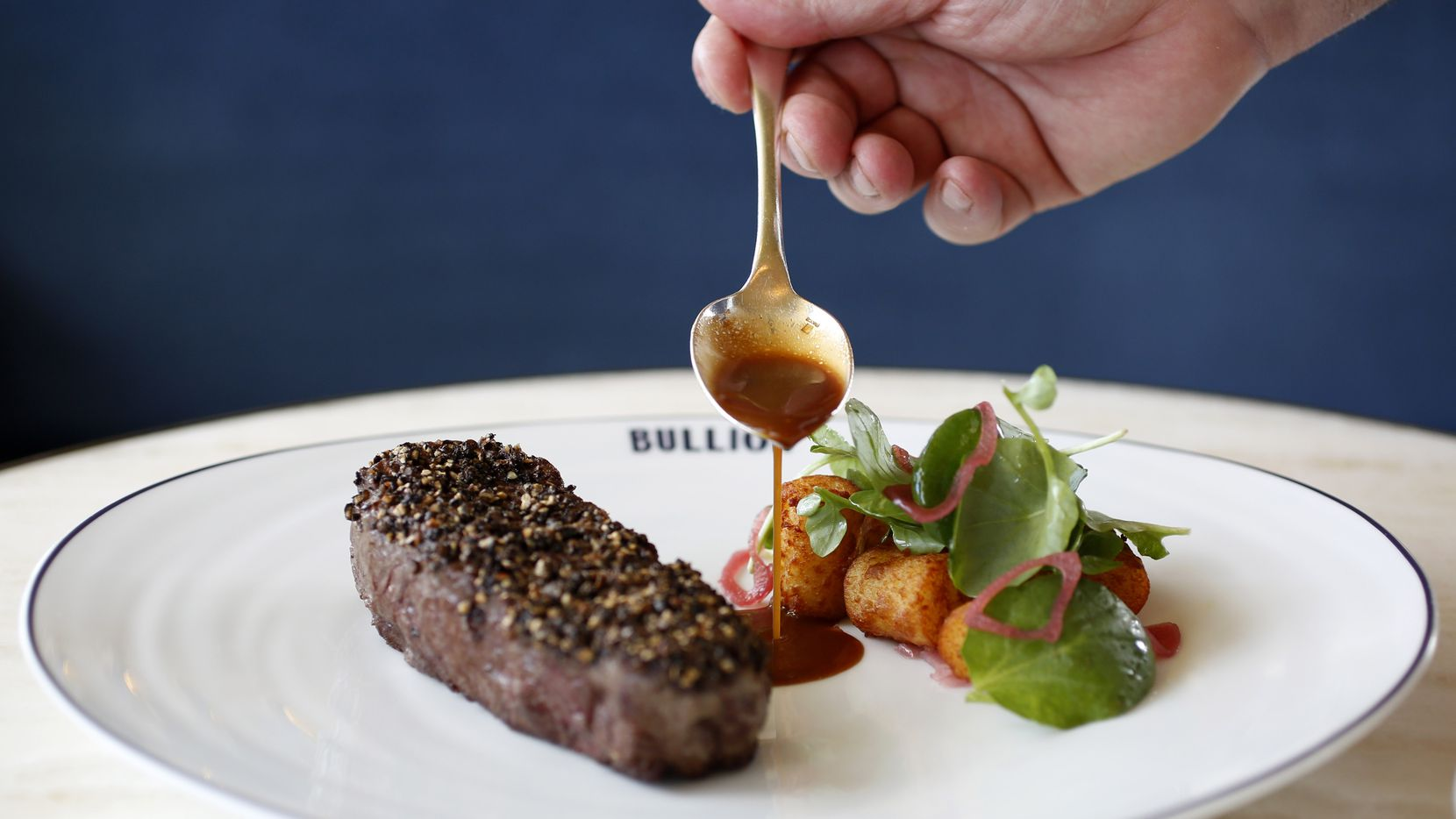 Chef Bruno Davaillon pours sauce on the Bison Au Poivre, photographed at Bullion in 2018. Founding executive chef Davaillon is stepping away from day-to-day operations at the downtown Dallas French restaurant.