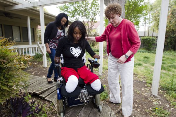 Whitney Mitchell heads to her mother Patricia Kirven's van to practice getting into the vehicle with physical therapist Kathy Mitchell (right) on Thursday.