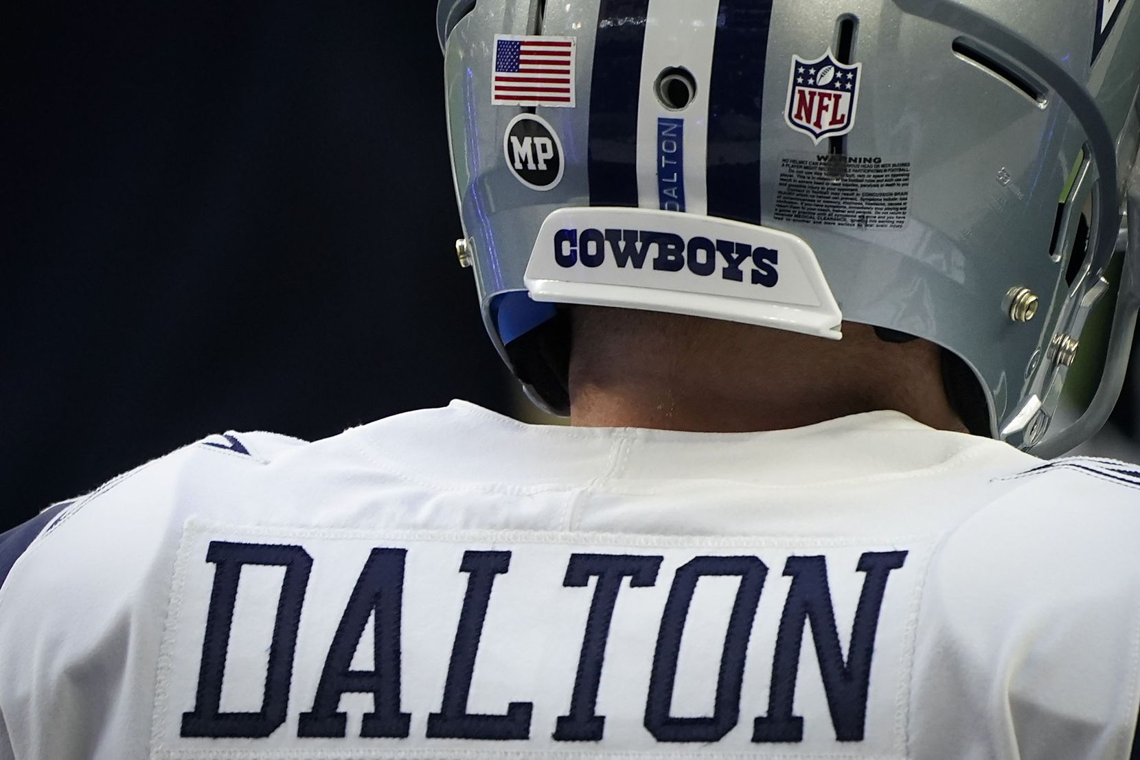 Dallas Cowboys quarterback Andy Dalton wears a sticker honoring strength and conditioning coach Markus Paul, who died Wednesday evening after having a medical emergency during Tuesday's practice, before an NFL football game at AT&T Stadium on Thursday, Nov. 26, 2020, in Arlington. (Smiley N. Pool/The Dallas Morning News)
