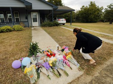 Anastasia Gonzalez of Burleson leaves flowers on the sidewalk in front of Atatiana Jefferson's home in Fort Worth.
