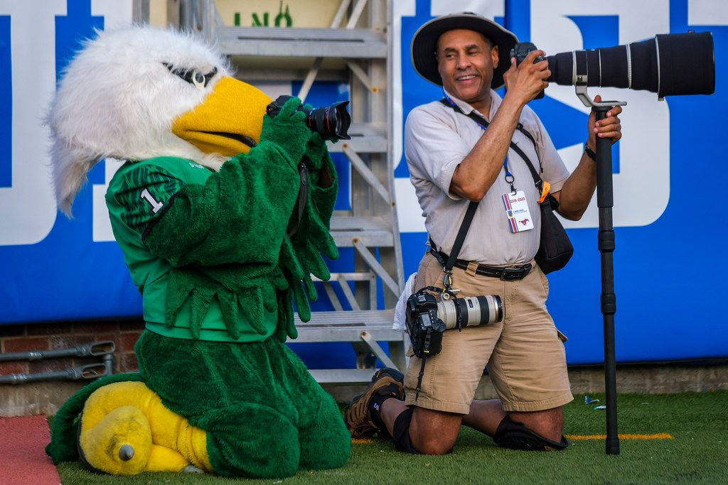 UNT mascot Scrappy shoots a photo with a camera borrowed from SMU athletics photographer Vladimir Cherry during the  first half of an NCAA football game at Ford Stadium on Saturday, Sept. 7, 2019, in Dallas. (Smiley N. Pool/The Dallas Morning News)