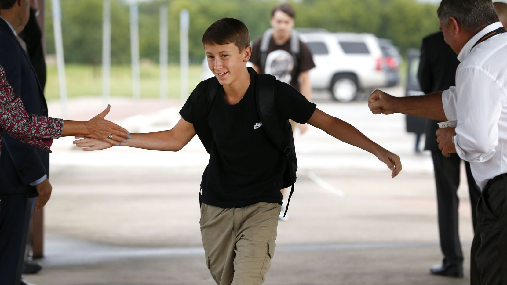 Freshman Wade Nicholson high-fives school and city administrators while walking in on the first day of school at Commerce High School.