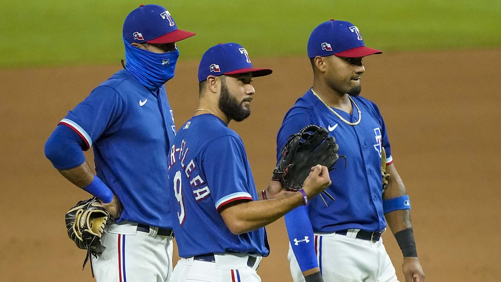 Texas Rangers infielder Isiah Kiner-Falefa (center) watches pitcher Derek Law warm up after a pitching change with Yadiel Rivera (left) and Andy Ibanez during the fifth inning of an exhibition game against the Colorado Rockies at Globe Life Field on Wednesday, July 22, 2020.