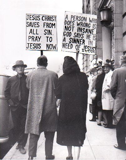 Picket signs carried by evangelist Edwin Tiemann and his wife bear placards decrying the use of psychiatry in a trial outside the Jack Ruby trial.
