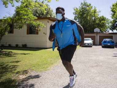 Mike Williams, a SMU defensive tackle, rushes back to his van after making deliveries while taking a summer job as an Amazon Prime delivery driver on May 29, 2020 in Midlothian.