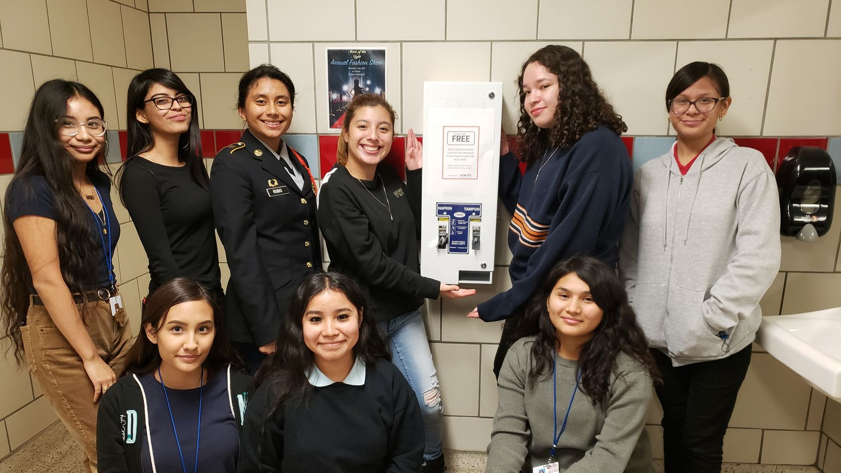 Members of Skyline High School's IGNITE club celebrate the installation of a feminine hygiene product dispenser in school's bathroom.