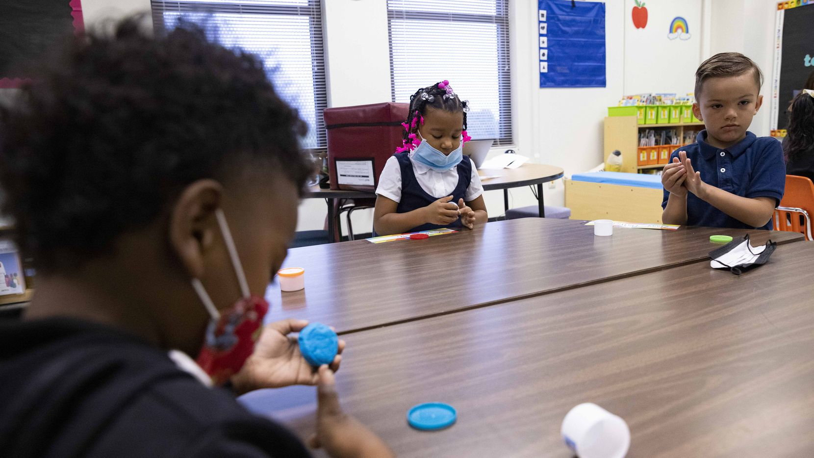 Mya Smith (center) and Ziggy Matherly (right) play with play-doh during the first day of school on Aug. 2, 2021, at H.I. Holland Elementary School in Dallas.
