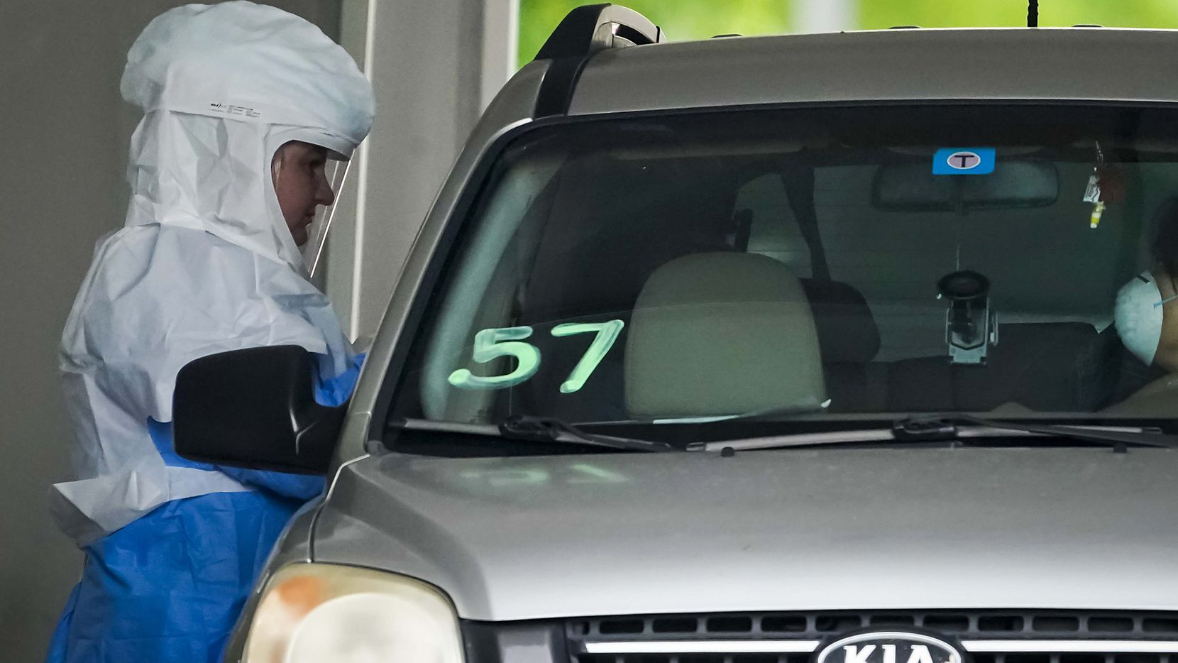 A healthcare worker screens the passenger of a vehicle at a Dallas County drive-thru COVID-19 testing center outside Ellis Davis Field House on Thursday, April 9, 2020, in Dallas.