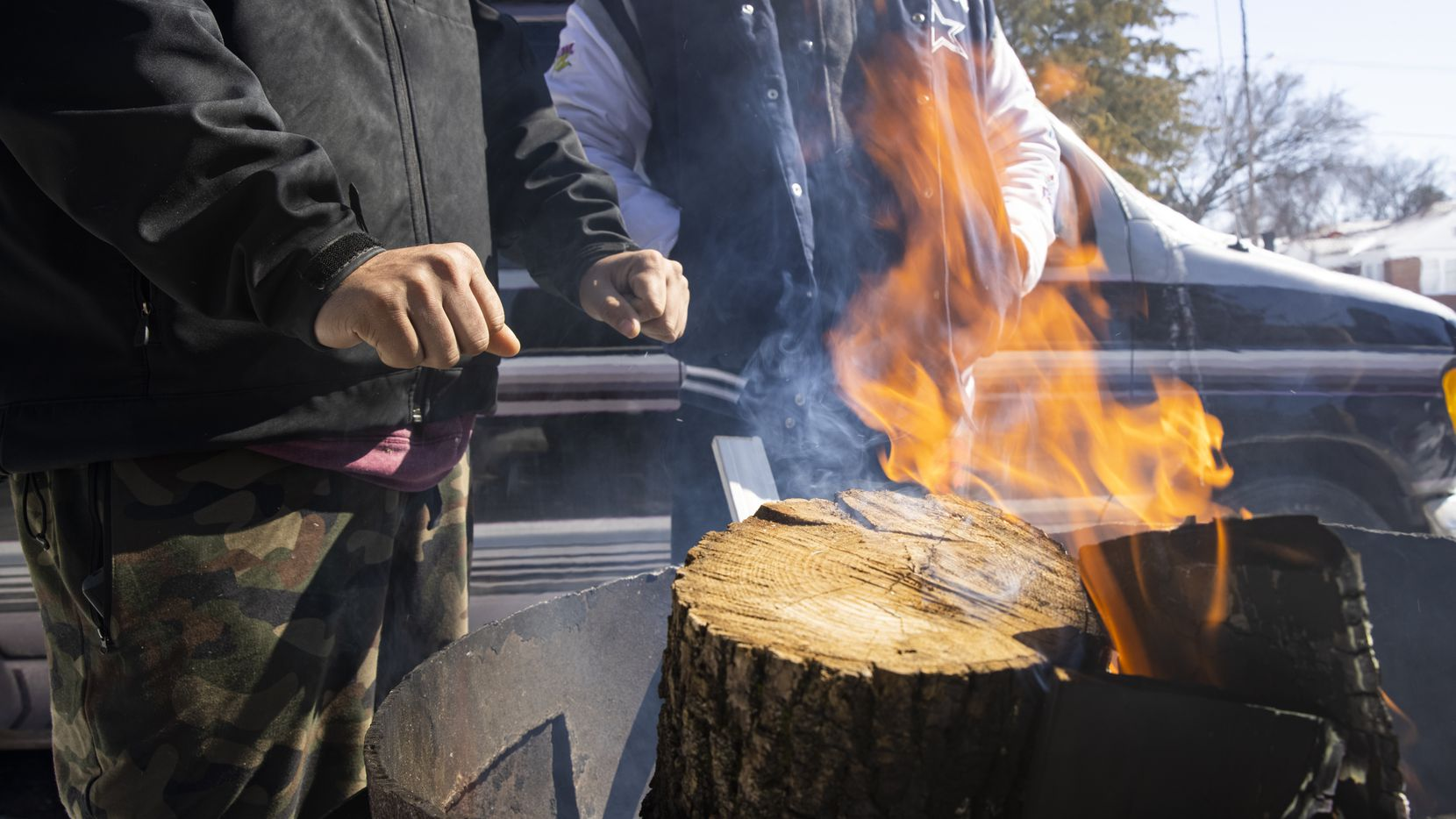 Alfredo Colon warms his hands over a fire in front of their East Dallas home on Monday. Mesquite will be distributing free firewood today beginning at 11 a.m.