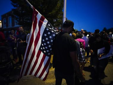 A large crowd of protestors, including a man carrying an upside-down American flag, gathered outside the house where Atatiana Jefferson was shot and killed, during a community vigil for Jefferson on Sunday, Oct. 13, 2019, in Fort Worth, Texas.  Jefferson, a 28-year-old black woman, was shot in her home by a white Fort Worth police officer during a welfare check.