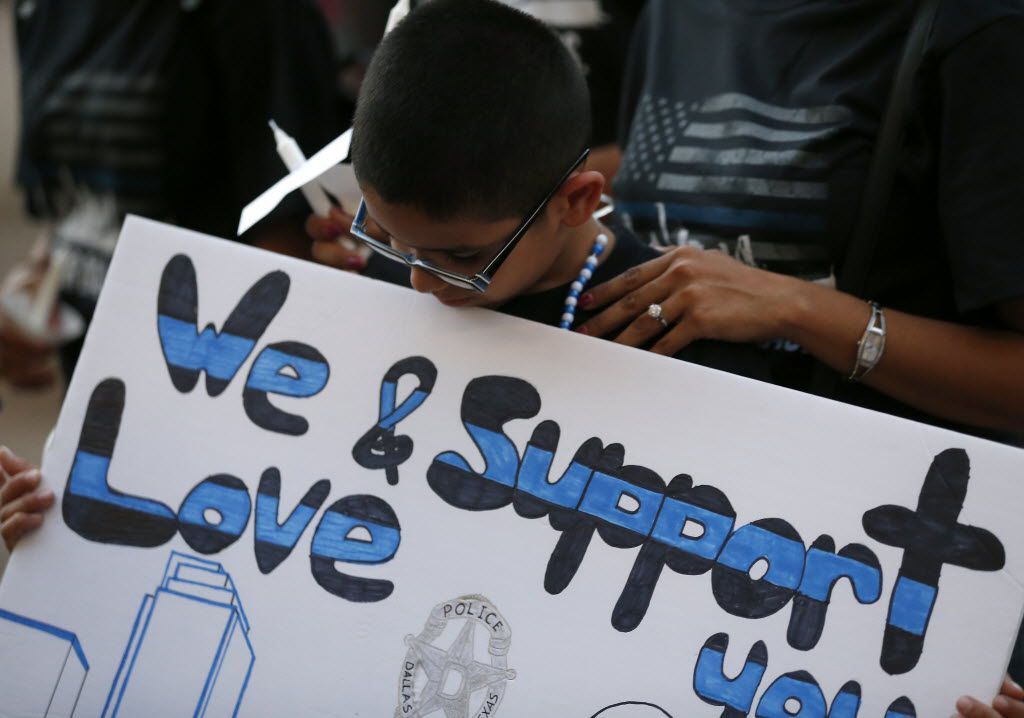 Ismael Beltran, 7, holds a sign during a candlelight vigil hosted by the Dallas Police Association in honor of the five police officers killed by the ambush attack in the line of duty at Dallas City Hall in downtown Dallas, Monday, July 11, 2016. (Jae S. Lee/The Dallas Morning News)