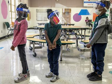 From left, Pre-K 4 students Alanna Ross, Jaliyah Webb, and Kendall Webb wait in a socially-distanced line after lunch in the cafeteria at N.W. Harllee Early Childhood Center in the Oak Cliff neighborhood of Dallas on Friday, Oct. 2, 2020. Dallas ISD's Pre-K numbers are down by the thousands to start the school year. (Lynda M. González/The Dallas Morning News)