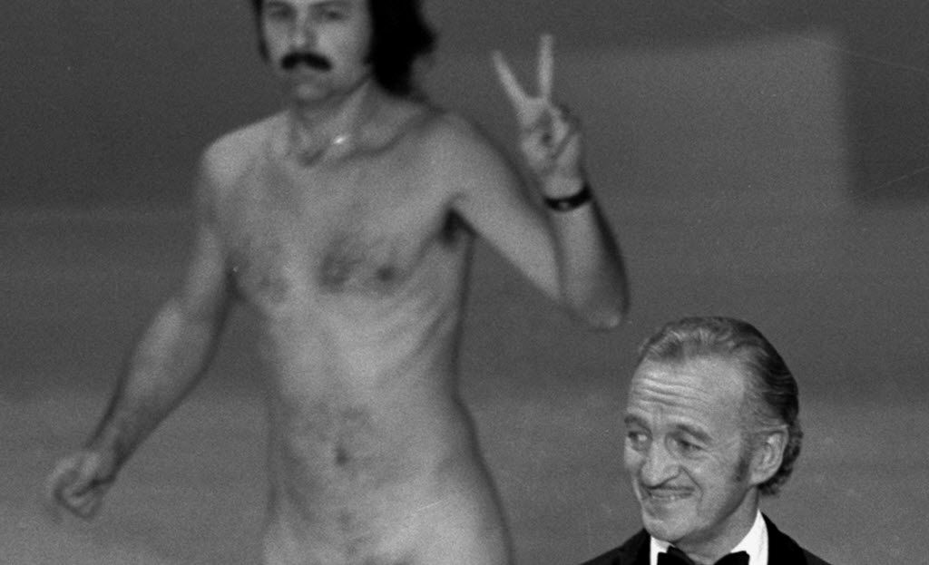 FILE - In this April 2, 1974 file photo, actor David Niven presents an award as streaker Robert Ope crosses the stage during the 1974 Academy Awards show in Los Angeles.  (AP Photo, file)