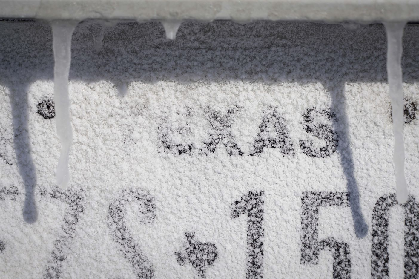 Icicles hang over a Texas license plate on a car after winter storm brought snow and freezing temperatures to North Texas on Monday, Feb. 15, 2021, in Richardson.  (Smiley N. Pool/The Dallas Morning News)