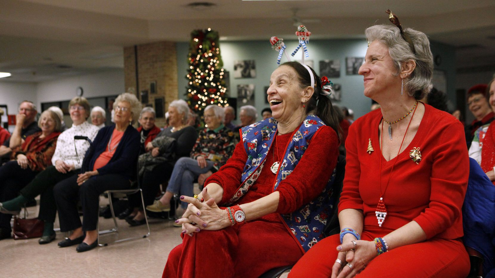 Susan Betz (left) and daughter Diana Betz laughed at a joke by Richardson Community Band conductor George Jones during a free holiday concert at the Richardson Senior Citizen Center on Dec. 10, 2014.
