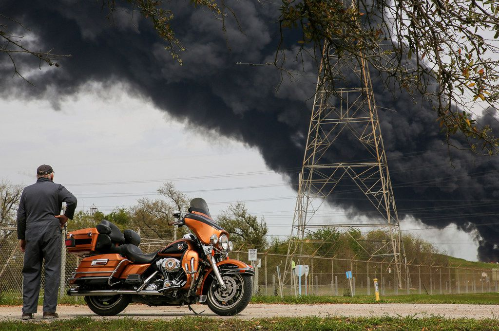 Bruce Bechtel, 64, stands next to his 2008 Harley-Davidson Ultra as he watches the plume of smoke caused by the petrochemical fire at the Intercontinental Terminals Company during his lunch break Monday, March 18, 2019, in Deer Park, Texas. The large fire at a Houston-area petrochemicals terminal will likely burn for another two days, authorities said Monday, noting that air quality around the facility was testing within normal guidelines.