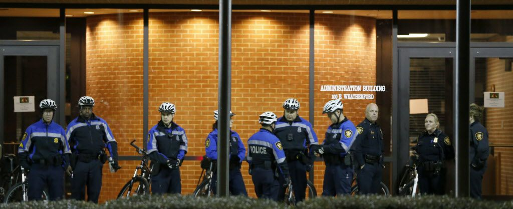 Police officers stand guard the Tarrant County Administration Building across Tarrant County Courthouse where protesters rally against police brutality in downtown Fort Worth, Texas, Thursday, Dec. 22, 2016.