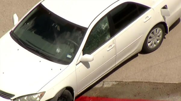 Footage captured by the KXAS-TV (NBC5) helicopter showed a white sedan with several bullet holes in the driver's side window stopped in an apartment complex parking lot in the 100 block of East Ash Lane.