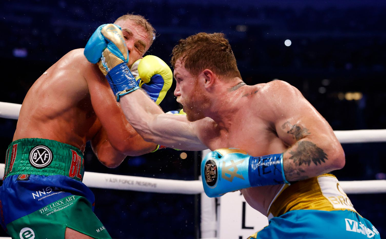 Boxer Canelo Alvarez (right) lands a punch on Billy Joe Saunders during their super middleweight title fight at AT&T Stadium in Arlington, Saturday, May 8, 2021. Saunders couldn't go beyond the eighth round because he sustained an eye injury and could not see. (Tom Fox/The Dallas Morning News)