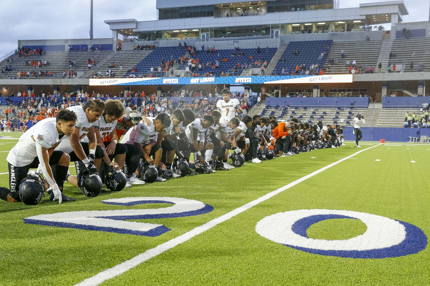 West Mesquite football players and coaches kneel at the 22 yard line in honor of former West Mesquite football player Aaron Lowe before a game against McKinney North at McKinney ISD Stadium on Thursday, Sept. 30, 2021, in Mckinney, Texas. Lowe was shot and killed on Sept. 26 in Salt Lake City, Utah. Lowe attended the University of Utah and played defensive back for the Utes. (Elias Valverde II/The Dallas Morning News)