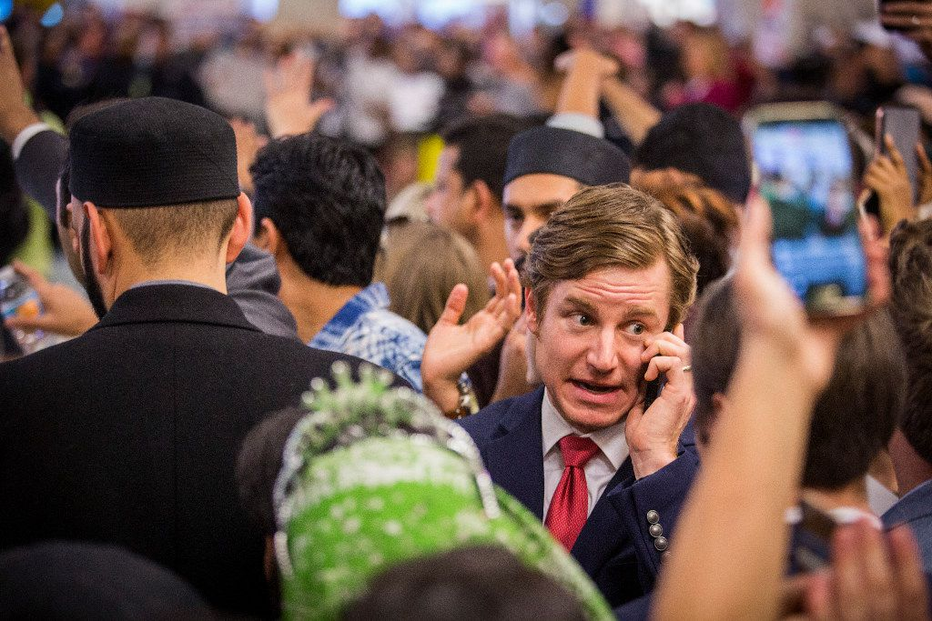 Attorney Chris Hamilton talks on his phone in a sea of protestors at DFW International Airport in opposition to President Donald Trump's executive order barring certain travelers on Sunday, Jan. 29, 2017. (Smiley N. Pool/The Dallas Morning News)
