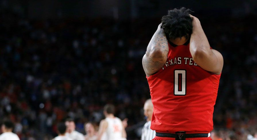 Texas Tech guard Kyler Edwards buries his face in his jersey after the Red Raiders' 85-77 overtime loss to the Virginia Cavaliers in the NCAA men's college basketball Final Four championship game Monday night at U.S. Bank Stadium in Minneapolis.