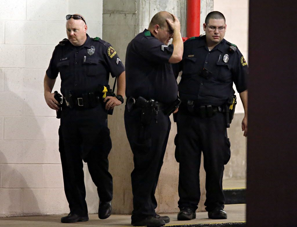 Dallas Police officers react  following a deadly shooting Friday, July 7, 2016 in Dallas. As a Black Lives Matter protest wound down, a gunman opened fire, shooting 11 police officers, killing five of them. (G.J. McCarthy/The Dallas Morning News)
