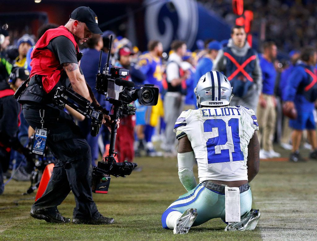 Dallas Cowboys running back Ezekiel Elliott (21) kneels on the sideline after narrowly completing a third quarter pass completion against the Los Angeles Rams in their NFC Divisional Playoff game at Los Angeles Memorial Coliseum in Los Angeles, Saturday, January 12, 2019. The Cowboys lost 30-22. (Tom Fox/The Dallas Morning News)