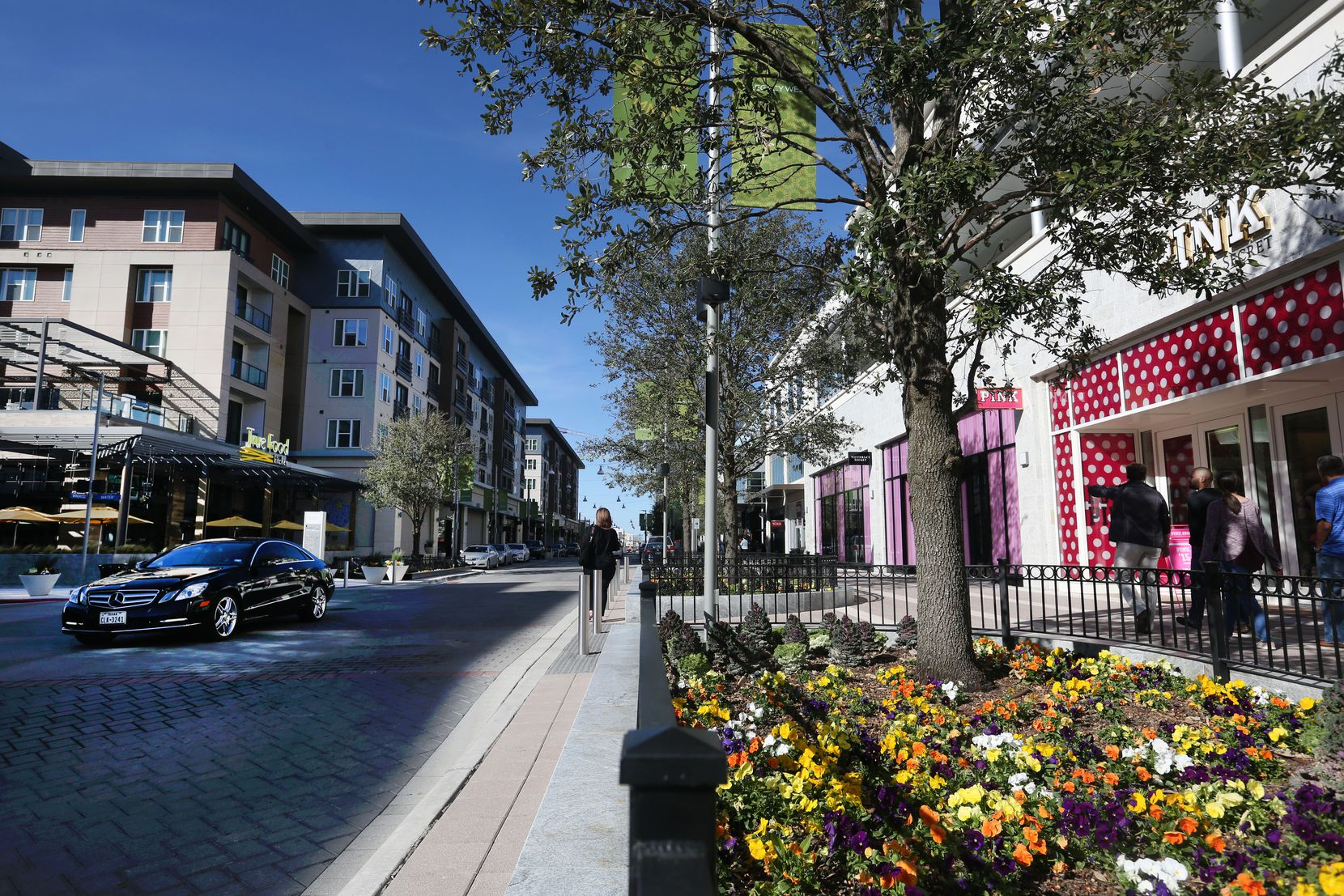Shoppers walk down the street at Legacy West in Plano.