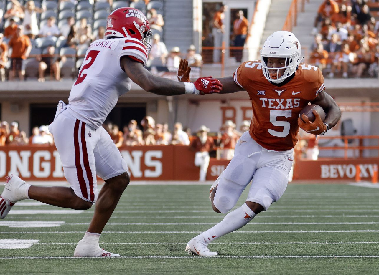 Texas Longhorns running back Bijan Robinson (5) gives a stiff arm to Louisiana-Lafayette Ragin Cajuns linebacker Lorenzo McCaskill (2) as he ran for the goal line during the third quarter at DKR-Texas Memorial Stadium in Austin, Saturday, September 4, 2021. He fumbled the ball but his teammate recovered the ball. (Tom Fox/The Dallas Morning News)