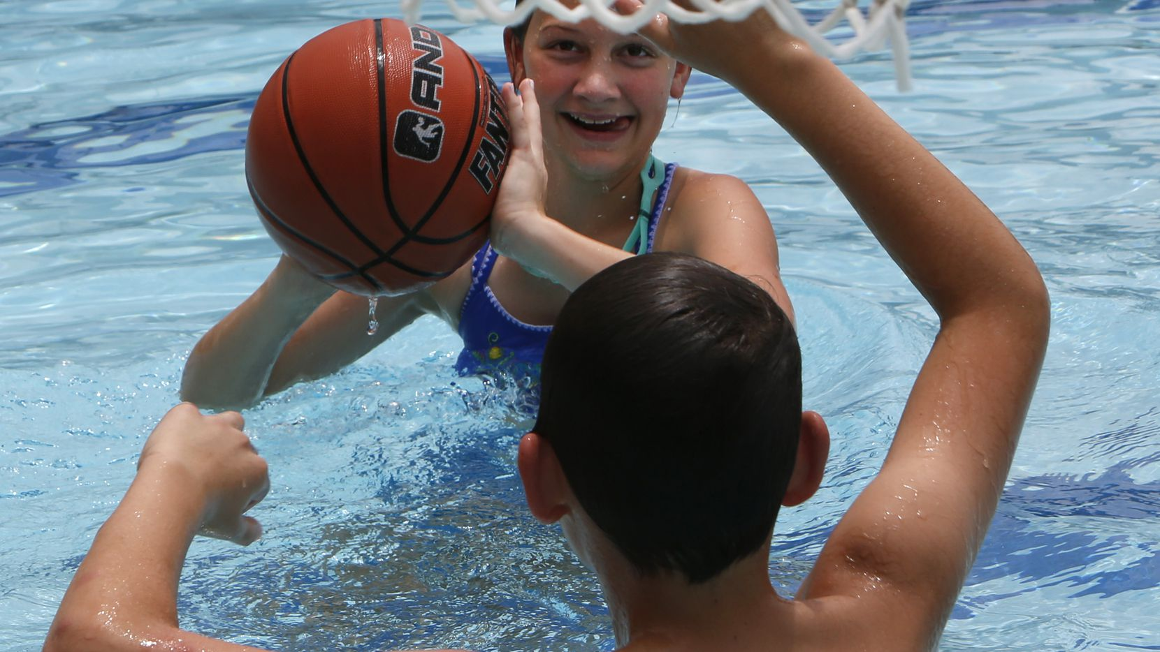 Emma Koelpin, 13, eyes a shot as she challenges her brother Elijah,11, to a game of poolside basketball. Beckie Koelpin joined her children and grandchild for swimming fun in the sun and water at the Lake Highlands Aquatic Center in Dallas on June 12, 2021.
