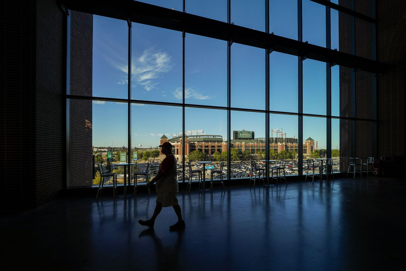 The old Globe Life Park, the former open-roofed home of the Texas Rangers, is seen through windows on the upper concourse of the new Globe Life Field in Arlington, Texas.